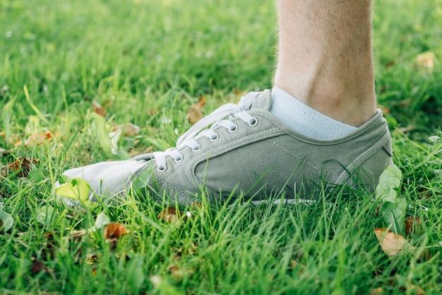 Piedi maschili in gumshoes grigi su erba Foto Premium