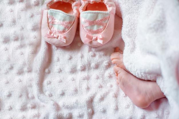 Piedi nudi di un neonato carino in una calda coltre bianca Foto Premium