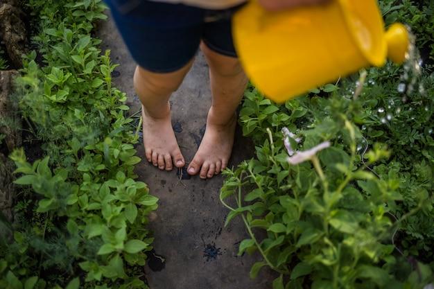 Piedi sporchi di una ragazza da vicino sul percorso in giardino Foto Premium
