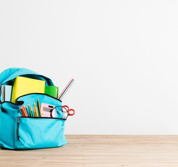 Pieno di articoli di cancelleria e libri zaino scuola blu Foto Gratuite
