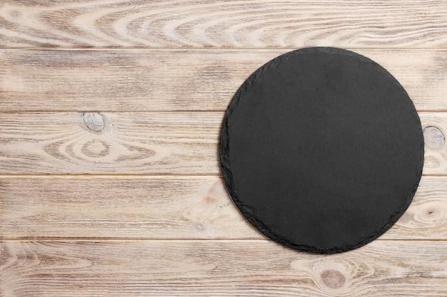 Pietra rotonda dell'ardesia nera su superficie di legno, vista superiore, spazio della copia Foto Premium