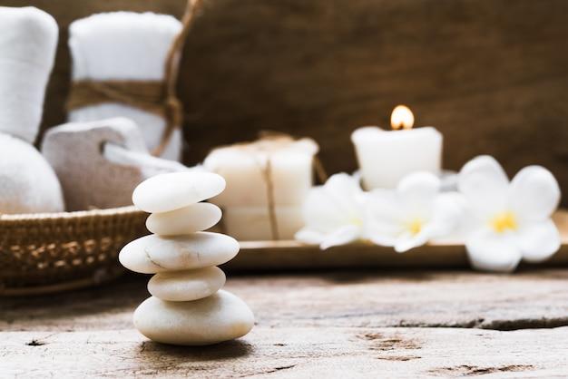 Pietre bianche zen e spa e trattamento con asciugamani, scrub, sapone di cocco e fiori di frangipane su fondo di legno rustico Foto Premium