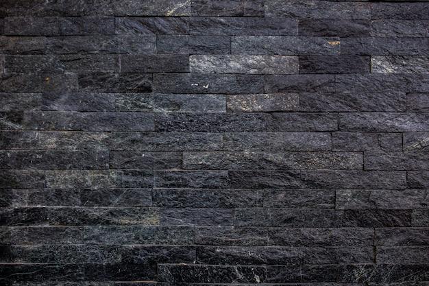 Pietre nere decorate sullo sfondo della parete Foto Premium