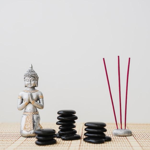 Pietre vulcaniche, bastoncini di incenso e figura di buddha Foto Gratuite