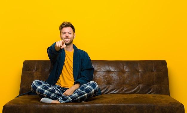 Pigiama da portare del giovane che indica alla macchina fotografica con un sorriso soddisfatto, sicuro, amichevole, scegliente. seduto su un divano Foto Premium