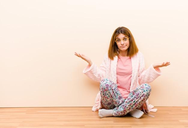 Pigiama da portare della giovane donna che si siede a casa che sembra sconcertato confuso e sollecitato chiedendosi fra le diverse opzioni sentirsi incerti Foto Premium