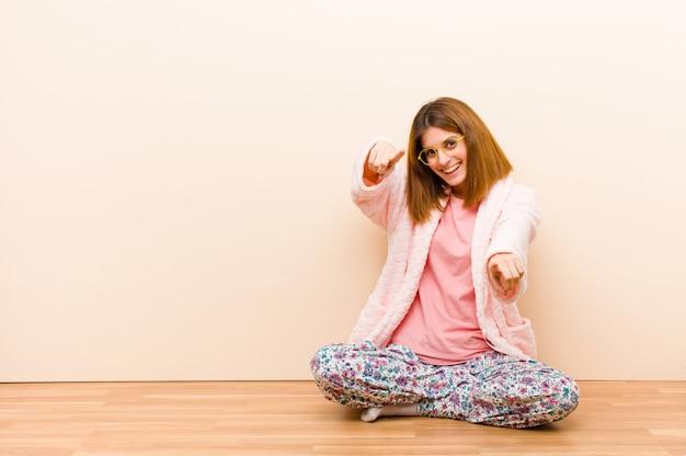 Pigiama da portare della giovane donna che si siede a casa sentendosi felice e sicuro, indicando la macchina fotografica con entrambe le mani e ridendo, scegliendovi Foto Premium