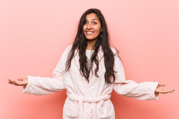 Pigiama da portare della giovane donna indiana che mostra un'espressione benvenuta. Foto Premium