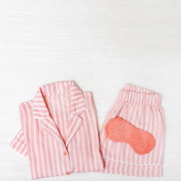 Pigiama rosa per ragazze, maschera per gli occhi per dormire su legno bianco. Foto Premium