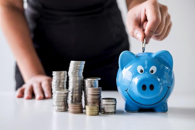 Pila accatastamento e mano mettendo le monete nel salvadanaio per pianificare la crescita Foto Premium