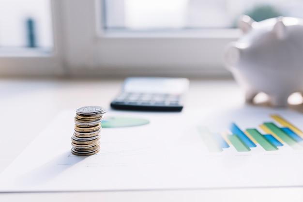 Pila della moneta sul grafico con il calcolatore e il porcellino salvadanaio sopra la tavola Foto Gratuite