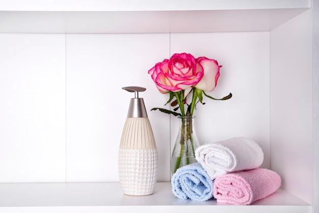 Pila di asciugamani con un dispenser di sapone e rose in vasein un primo piano del bagno Foto Premium