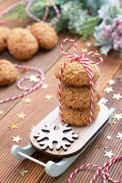 Pila di biscotti di farina d'avena casalinghi sulla slitta. biscotti sani di natale, biscotti. tavolo in legno rustico. decorazione invernale. Foto Premium