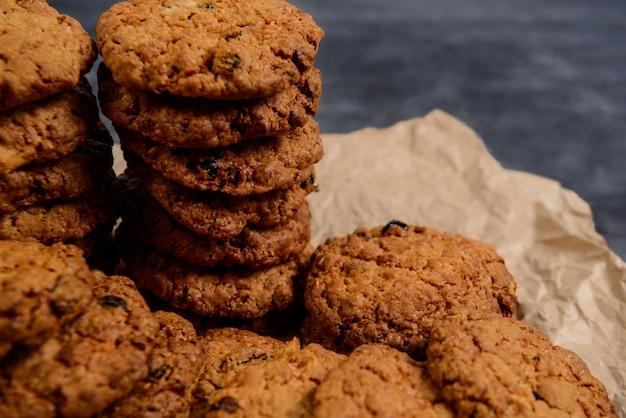 Pila di biscotti di farina d'avena dolci sulla carta di cottura alla tavola di legno Foto Gratuite