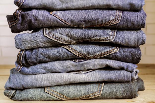 Pila di blue jeans sullo scaffale di legno. concetto di abbigliamento di bellezza e moda Foto Premium