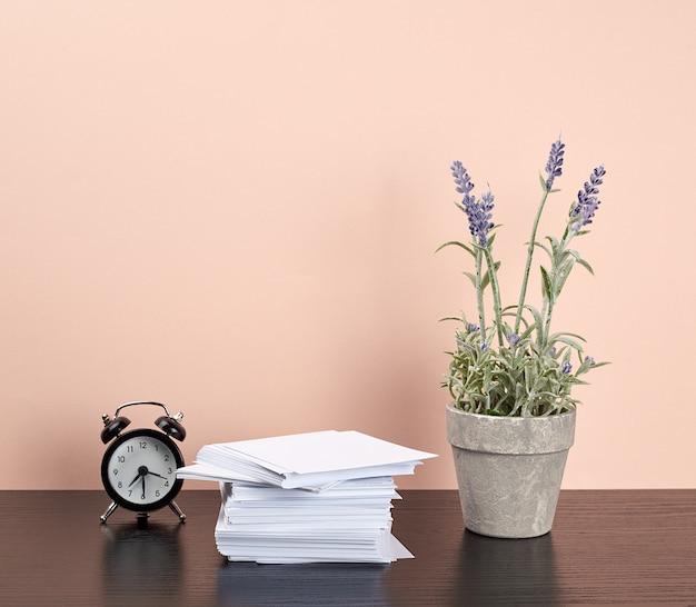 Pila di carte quadrate bianche, una pentola in ceramica di lavanda e una sveglia Foto Premium