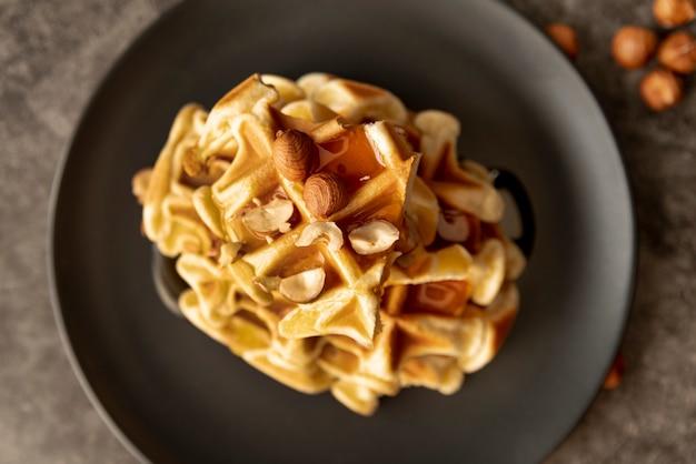 Pila di cialde sul piatto con miele e nocciole Foto Gratuite