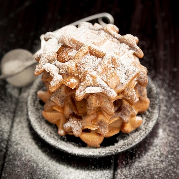 Pila di cialde sul piatto con zucchero a velo Foto Gratuite