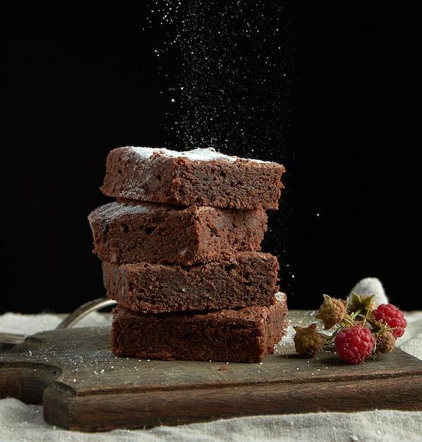 Pila di fette quadrate al forno del dolce di cioccolato del brownie spruzzate con zucchero bianco Foto Premium