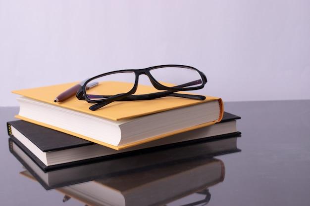 Pila di libri su sfondo bianco con gli occhiali. concetto di world book day. Foto Premium