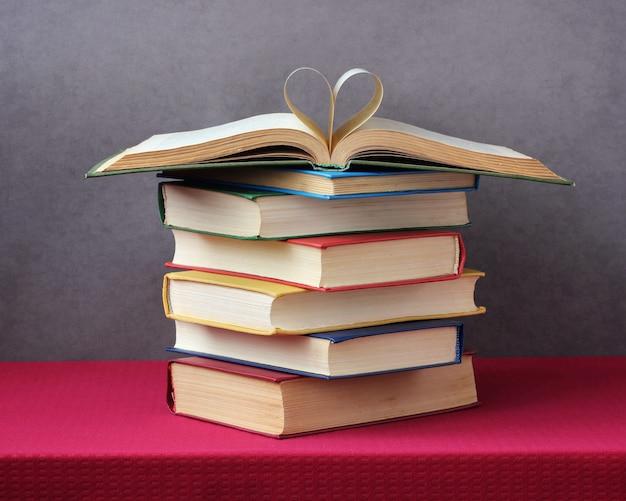 Pila di libri sul tavolo con una tovaglia rossa. Foto Premium