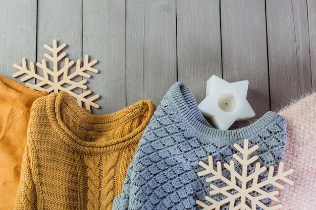 Pila di maglioni a maglia accoglienti bianchi su un tavolo di legno Foto Premium