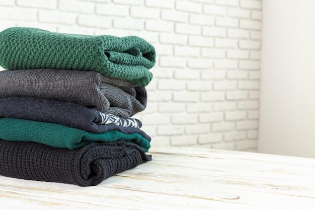 Pila di maglioni lavorati a maglia bianchi accoglienti Foto Premium