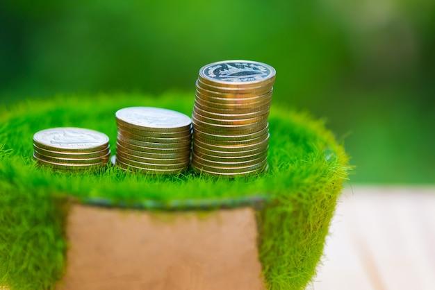 Pila di moneta d'oro su erba artificiale in vaso Foto Premium