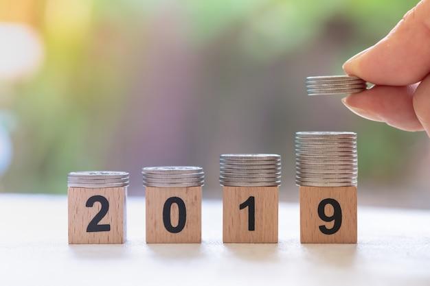 Pila di monete d'argento sul blocco di legno numero 2019 con man mano che tiene e mettere pila di monete in cima Foto Premium