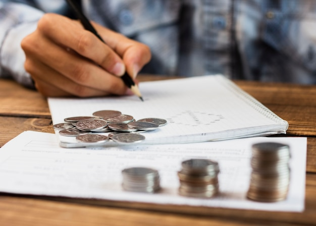 Pila di monete di risparmio che contano momento Foto Gratuite