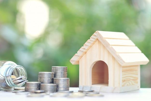 Pila di monete monete e casa modello Foto Premium