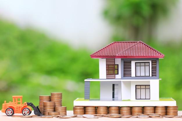 Pila di monete soldi e camion giocattolo su sfondo verde naturale Foto Premium
