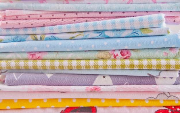 Pila di nuovi tessuti in diversi colori panno sul tavolo di legno Foto Premium