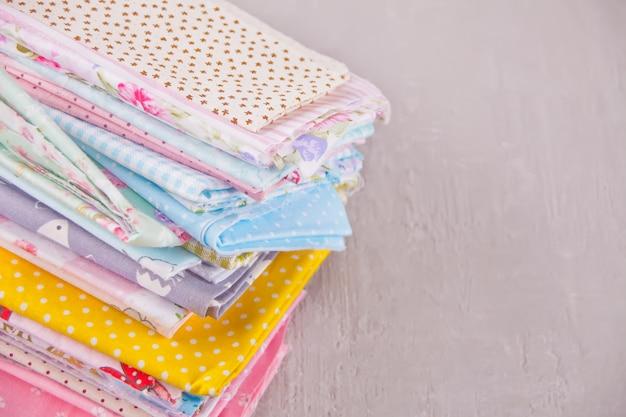 Pila di nuovi tessuti in diversi colori panno sul tavolo Foto Premium