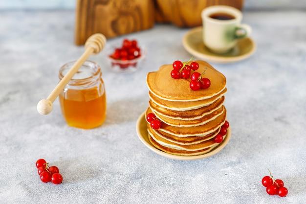Pila di pancake fatti in casa con sciroppo di miele e frutti di bosco. Foto Gratuite