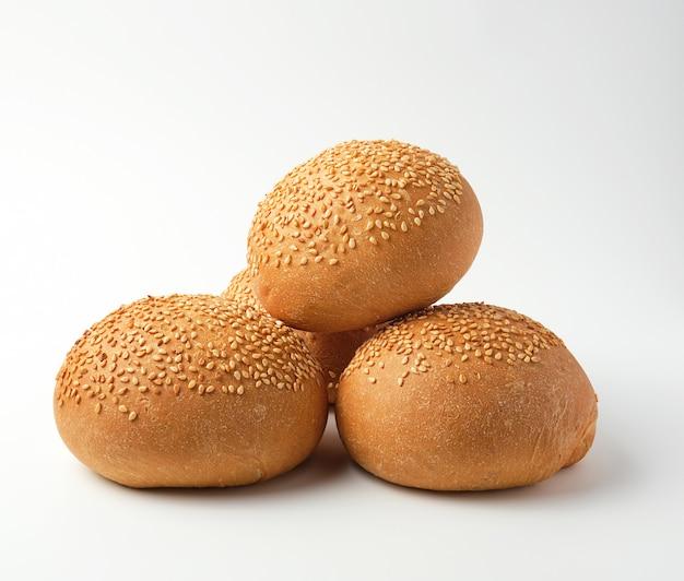Pila di panino intero tondo al forno con semi di sesamo a base di farina di grano bianco Foto Premium