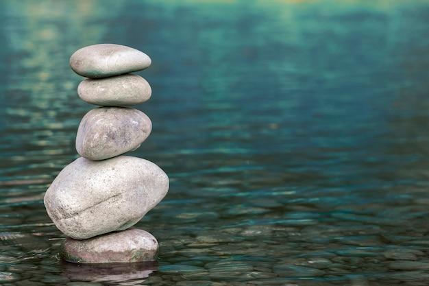 Pila di pietre che equilibrano in cima in acqua blu del fiume Foto Premium
