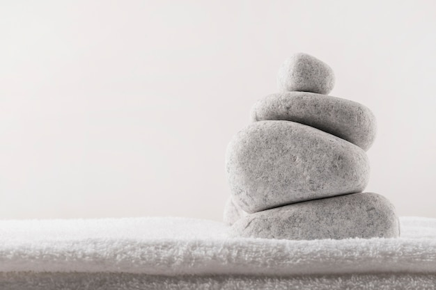 Pila di pietre spa su morbido asciugamano piegato su sfondo bianco Foto Gratuite
