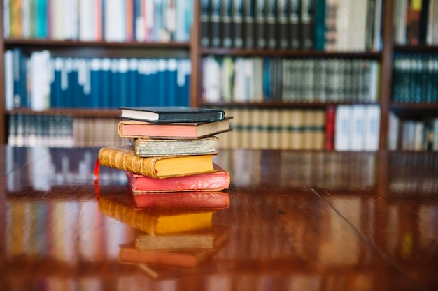 Pila di vecchi libri sul tavolo della biblioteca Foto Gratuite