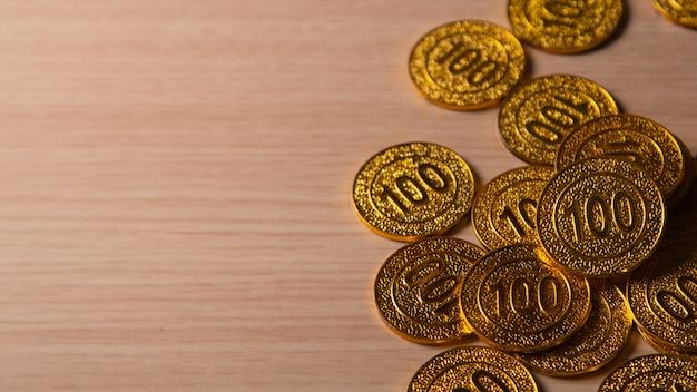 Pila dorata delle monete sullo spazio di legno della copia del qith Foto Premium