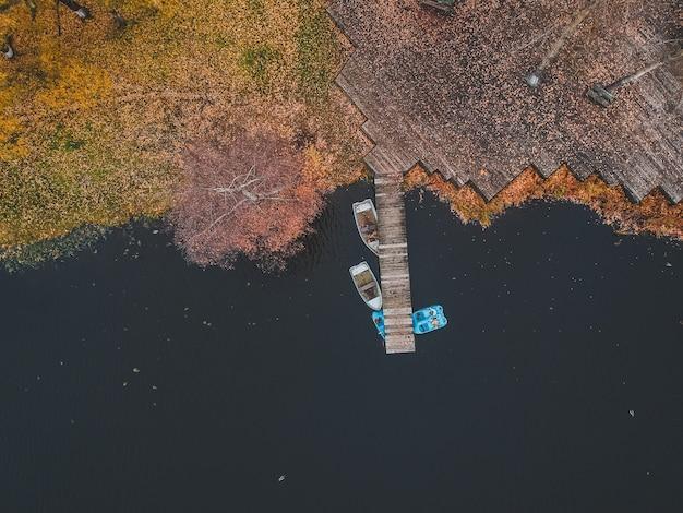 Pilastro di vista aerea con le barche di legno sulla riva di un lago pittoresco, foresta di autunno. san pietroburgo, russia. Foto Premium