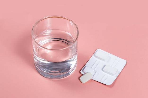 Pillole antibatteriche vaginali bianche su sfondo rosa le candele vengono immerse in acqua e iniettate nella vagina per trattare la candidosi, il mughetto, l'infiammazione. farmaco moderno efficace per il trattamento delle malattie Foto Premium