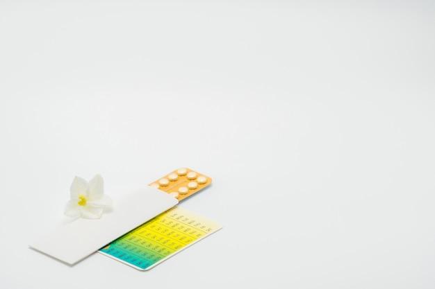 Pillole anticoncezionali o pillola contraccettiva con astuccio di carta e fiore bianco su fondo bianco. concetto di pianificazione familiare. terapia ormonale sostitutiva. trattamento dell'acne ormonale con pillola anti-androgena. Foto Premium