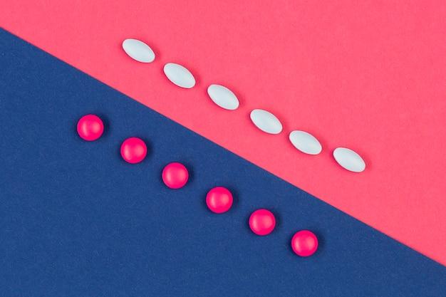 Pillole bianche e rosa sulla scrivania Foto Gratuite