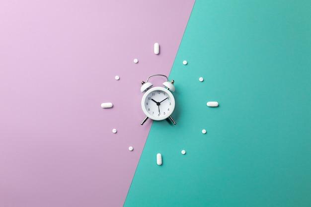Pillole, compresse e sveglia bianca su verde e viola Foto Premium