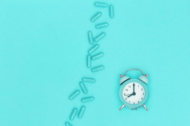 Pillole di medicina farmaceutica, capsula e orologio per controllo del tempo si trovano su carta color menta. assistenza sanitaria. sfondo medico. vista dall'alto. copia spazio Foto Premium