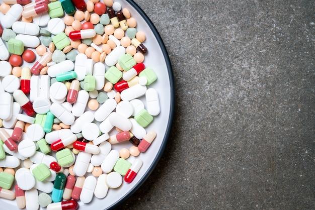 Pillole, droghe, farmacia, medicina o medico sul piatto Foto Premium