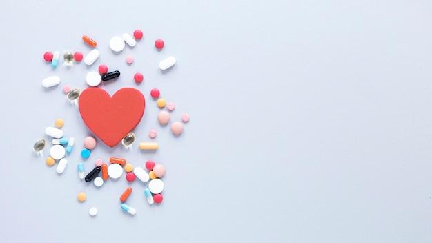 Pillole e cuore di vista superiore con lo spazio della copia Foto Gratuite