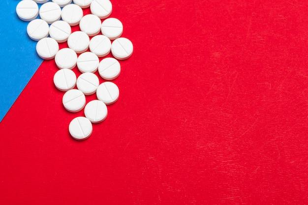 Pillole mediche bianche su una priorità bassa rossa e blu di due colori Foto Premium