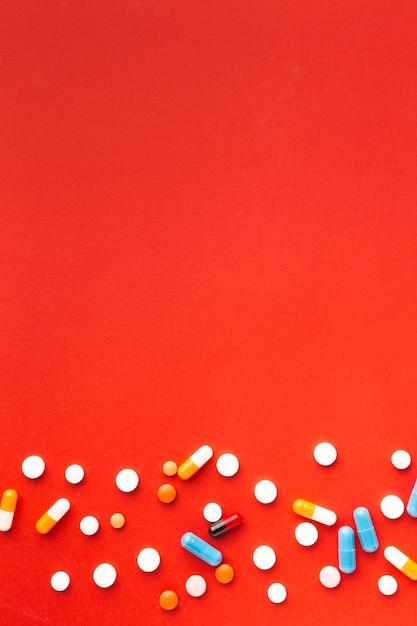 Pillole mediche variopinte e fondo rosso dello spazio della copia Foto Gratuite